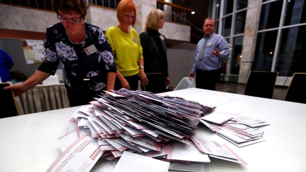 Election officials open ballot boxes during the general election in Riga, Latvia October 6, 2018.