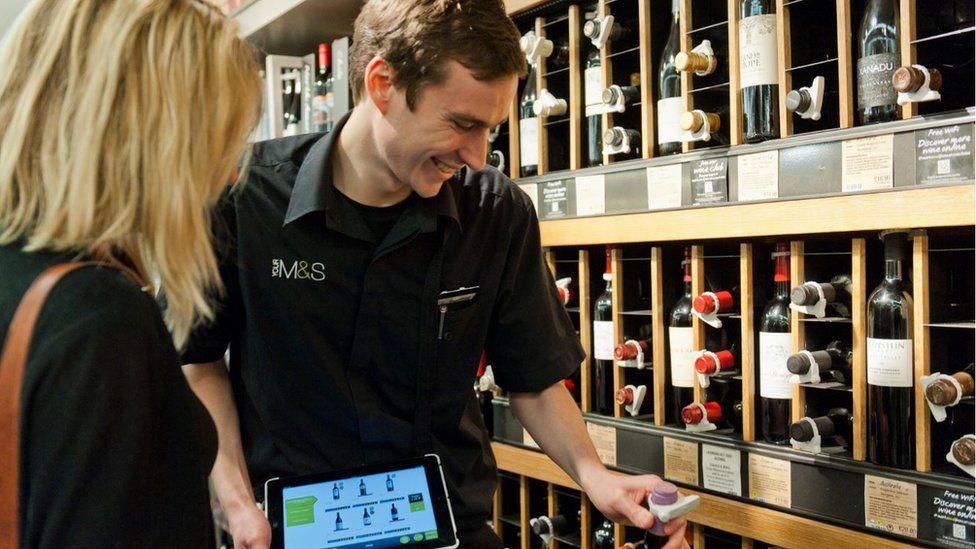 An M&S employee helping a customer choose wine