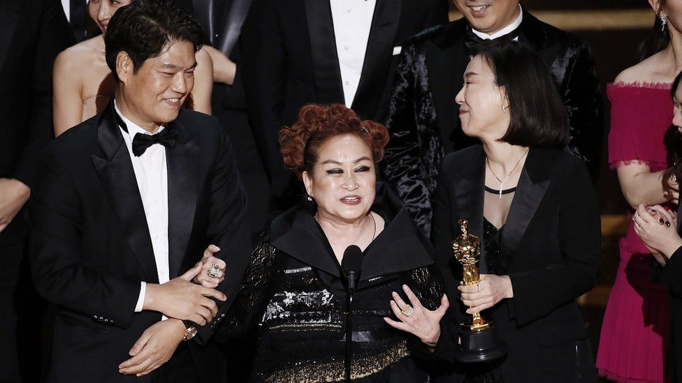 Miky Lee (centre) speaks at the Oscars