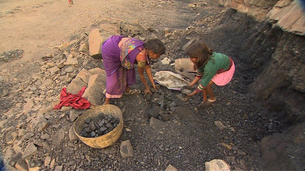 Two little girls working at a coal mine in India