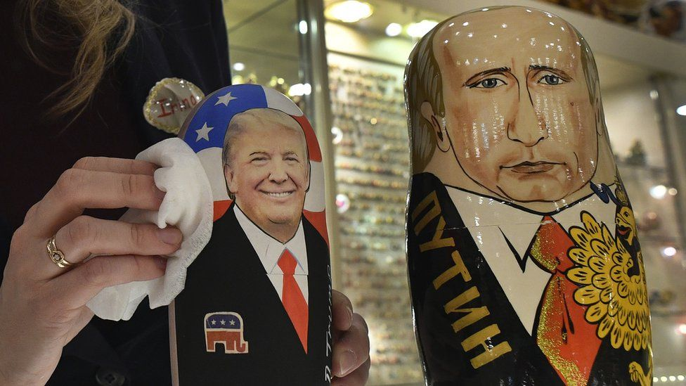 An employee polishes wooden Russian tolls depicting the faces of Donald Trump and Vladimir Putin at a shop in Moscow.