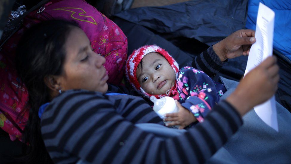 Lila lies with her 10-month-old daughter Sofia from Honduras and reads information about claiming asylum in the US as she rests in a temporary shelter in Tijuana, Mexico, 23 November
