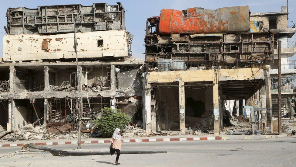 A girl crosses a street in front of buildings topped by damaged buses, which act as barricades to provide protection from government snipers, in Aleppo's Old City (18 October 2015)