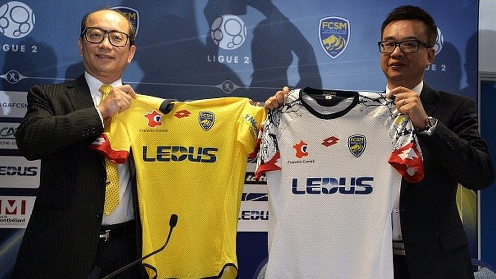 Li Wing-Sang, CEO of Hong-Kong based lighting company Ledus, and financial director Chi Hung Chiu show the new jerseys of Sochaux's football club
