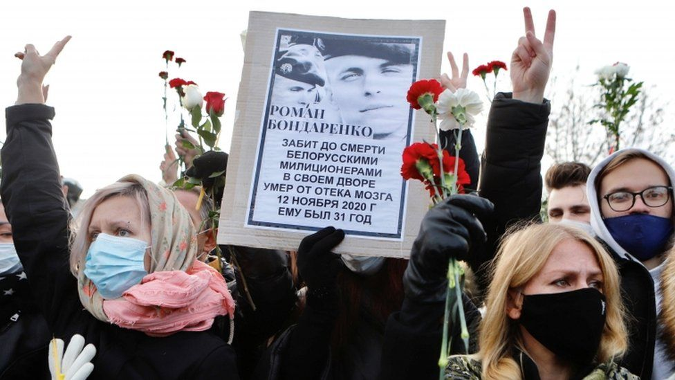 People hold a portrait of Roman Bondarenko, an anti-government protester who died in hospital following what witnesses said was a severe beating by security forces, during a memorial service in his honour, in Minsk, Belarus November 20, 2020