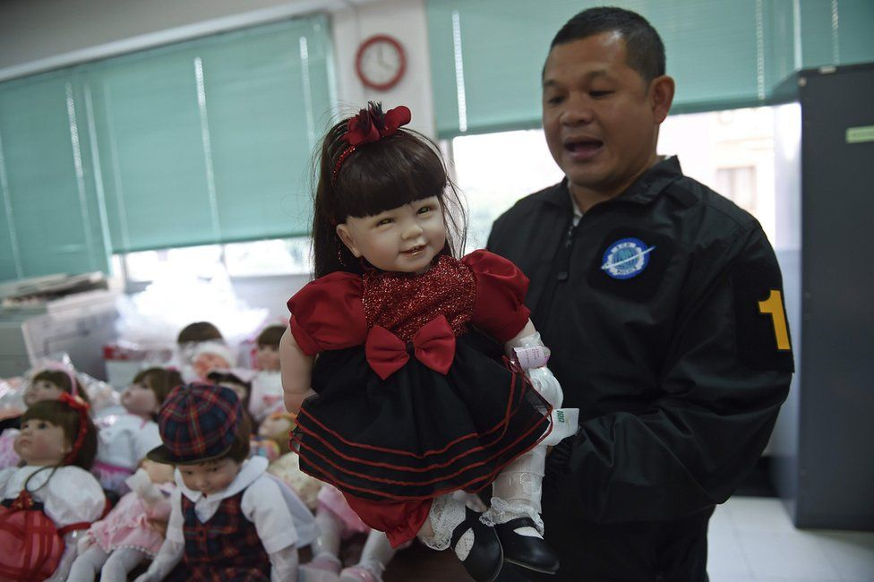 """Thai policeman shows a """"luk thep"""" (child angel) doll after more than a hundred of them were seized in separate raids, at the Economic Crime Suppression Division in Bangkok on 26 January 2016."""