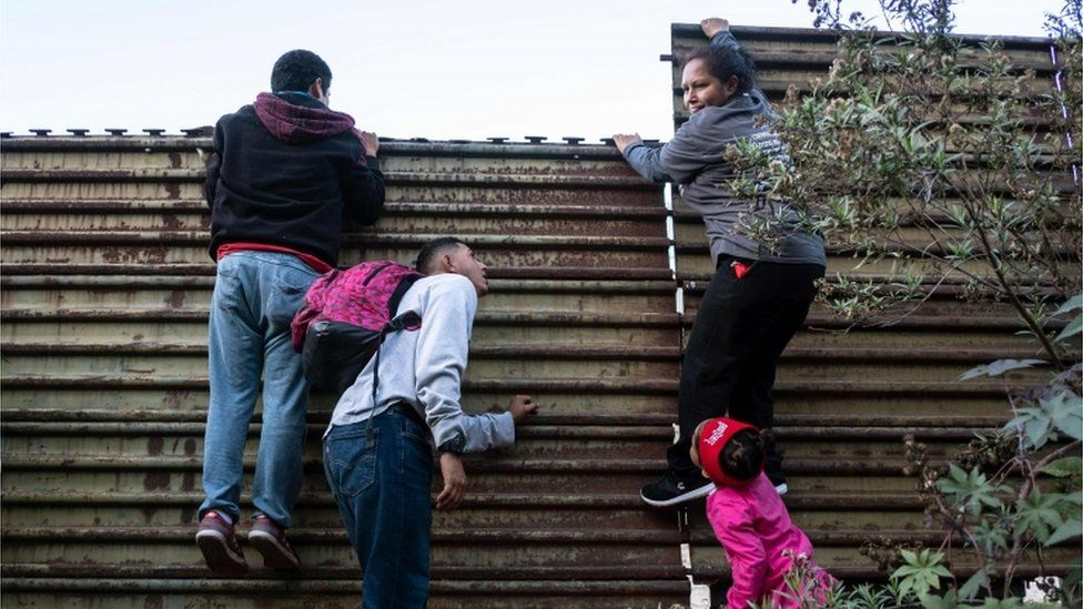 Honduran migrants try to climb the Mexico-US border fence to cross to San Diego County