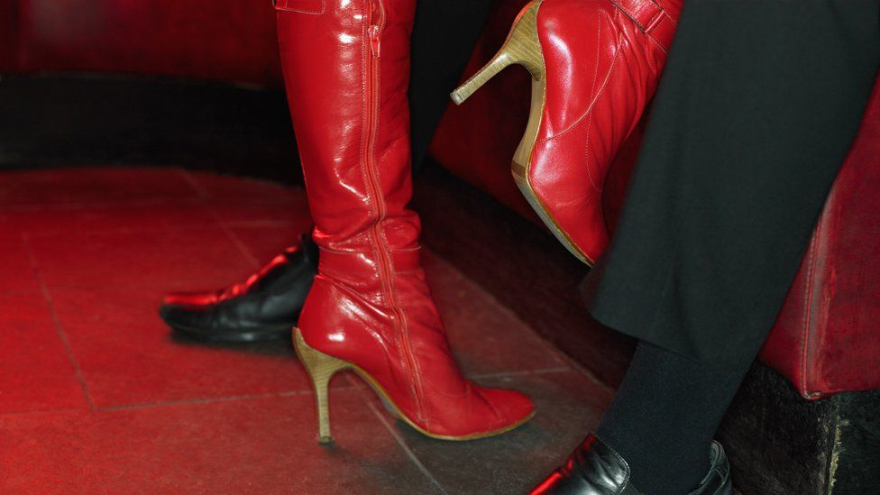 A shot of a stripper's boots as she performs a private dance