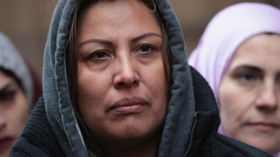 Francisca Lino listens as Rep. Luis Gutierrez speaks to the press after leaving the office of Immigration Services where he was briefly handcuffed and detained on 13 March, 2017 in Chicago