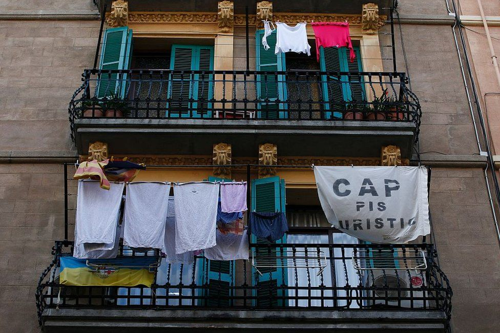"""A banner reading """"No tourist flats"""" hangs from a balcony to protest against holiday rental apartments for tourists in Barcelona on 24 November, 2016"""
