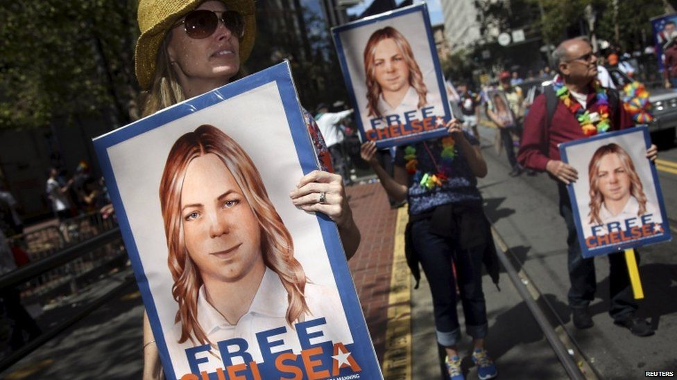 People hold signs calling for the release of imprisoned wikileaks whistleblower Chelsea Manning while marching in a gay pride parade in San Francisco, California on 28 June 2015.