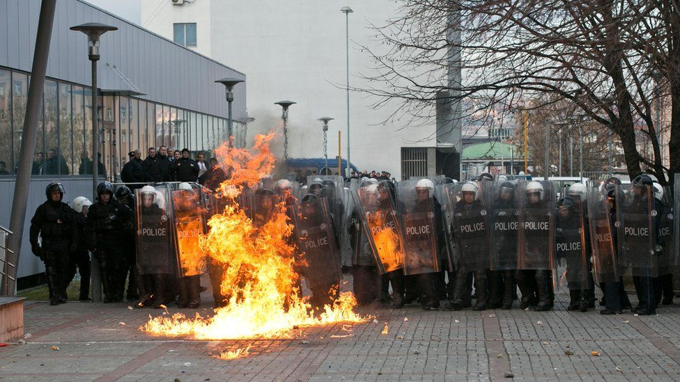Pristina police in front of a fire caused by a petrol bomb (9 January)