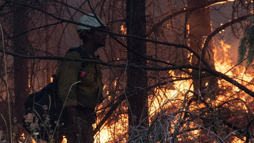 A firefighter stands next to a fire in Oregon, US