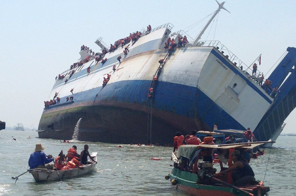 The passengers and crew of the KM Wihan Sejahtera abandon ship