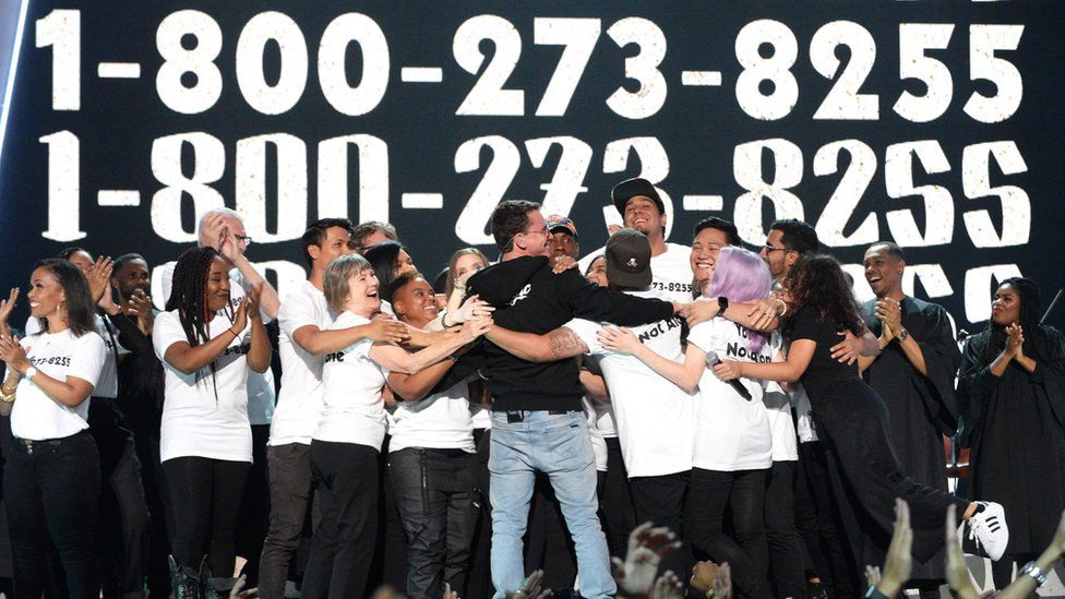 Logic hugs survivors of suicide on stage, with the helpline number clearly visible on shirts and screen behind