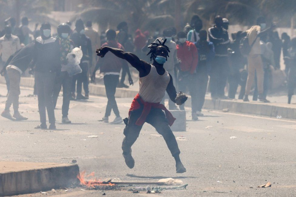 A supporter of opposition leader Ousmane Sonko hurls stones during clashes with security forces.