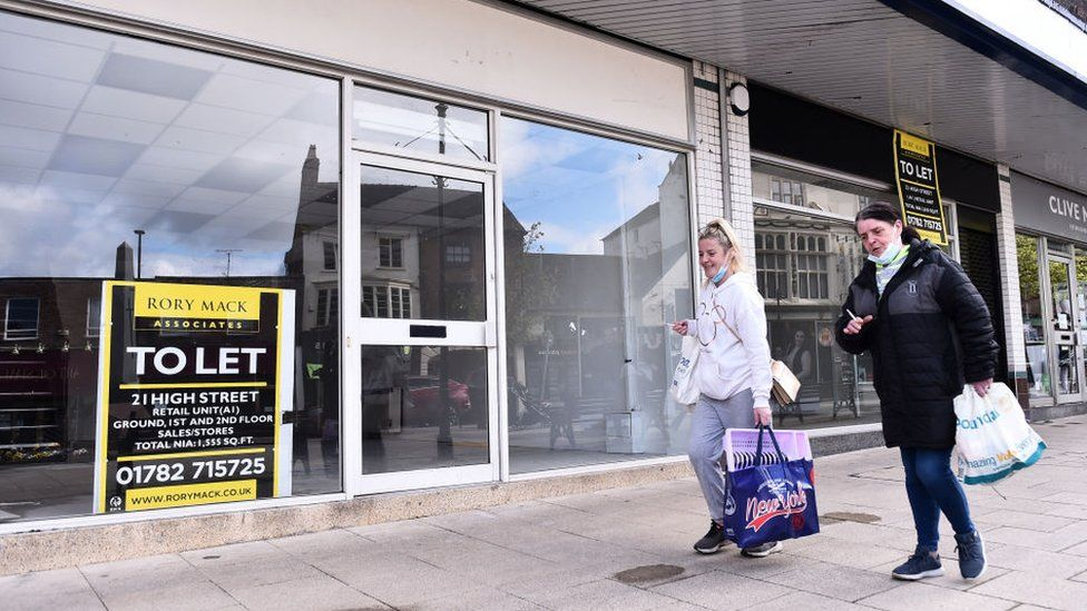 Women walk past empty retail units with To Let signs
