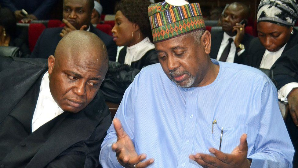 Former national security adviser of ex-president Goodluck Jonathan, Sambo Dasuki (R), speaks with his lawyer Ahmed Raji, during his trial at the federal high court in Abuja,