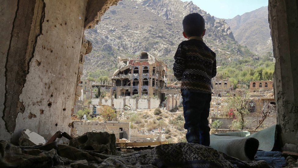 A photo taken on March 18, 2018, shows a Yemeni child looking out at buildings that were damaged in an air strike in the southern Yemeni city of Taez