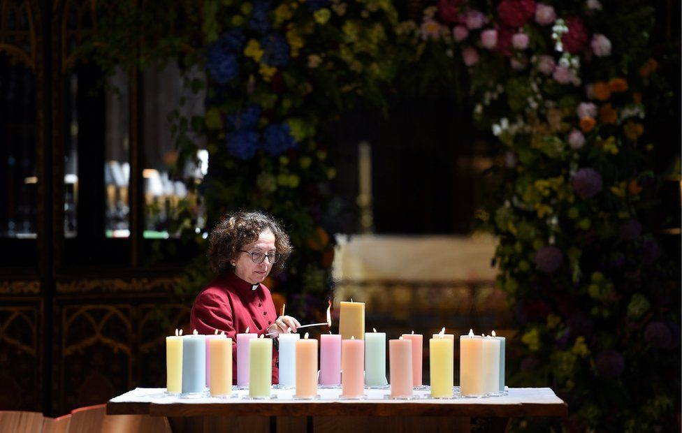 A member of the clergy lights candles for the victims of Mancester Arena attack, ahead of The Manchester Arena National Service of Commemoration at Manchester Cathedral in central Manchester, Britain May 22, 2018