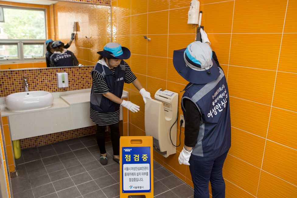 Two women checking toilets in Seoul