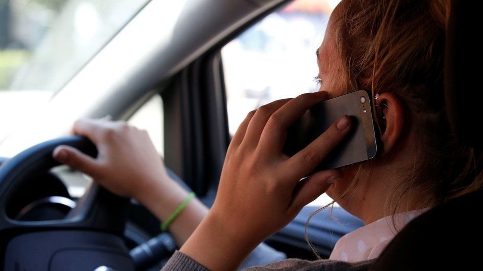 Woman using a mobile phone in the car