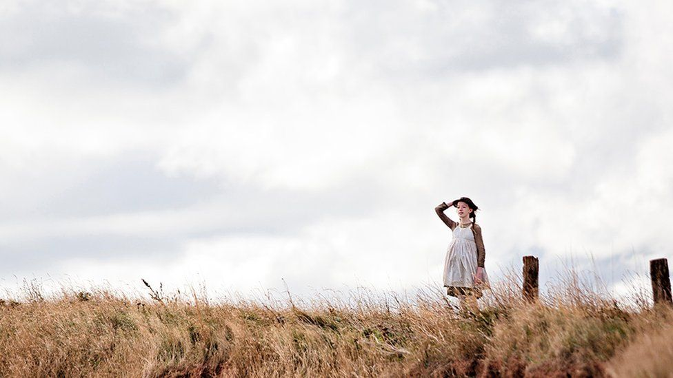 Anne stands on the Cliffs of Prince Edward Island