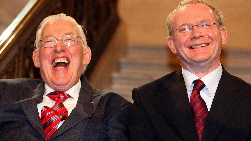 Ian Paisley and Martin McGuinness smile after being sworn in as first and deputy first ministers of the Northern Ireland Assembly