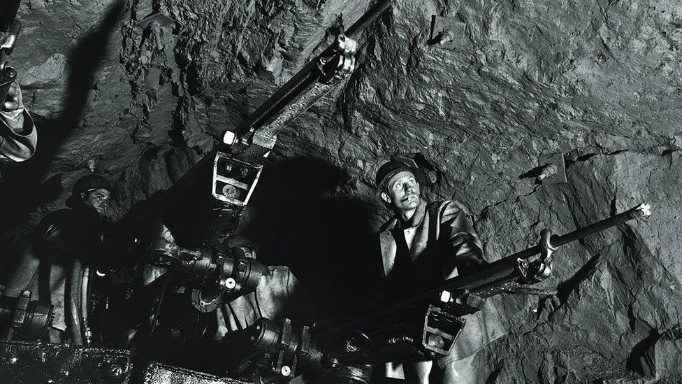 Diggers in an underground tunnel