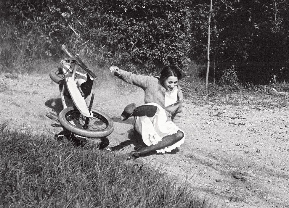 A woman falls off a go-kart whilst laughing
