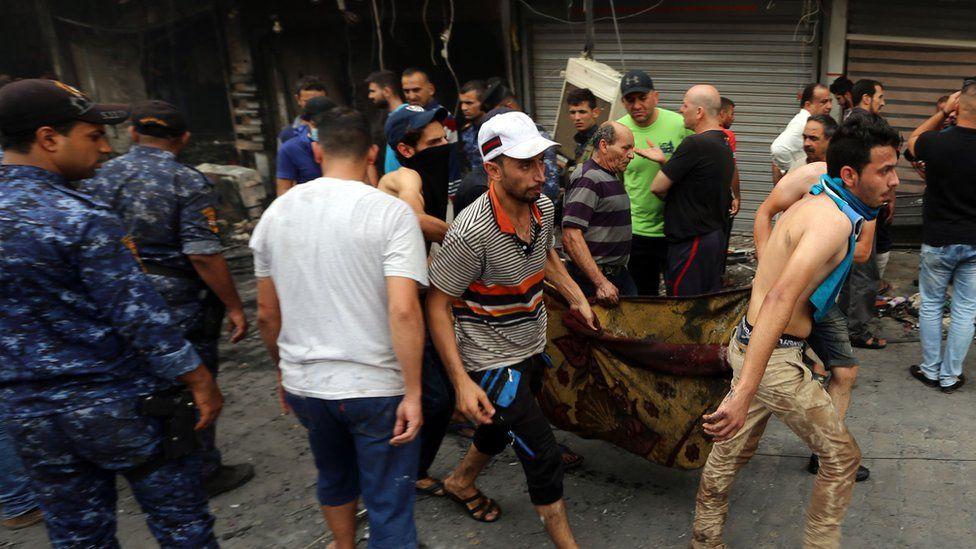 Iraqis evacuate body from site of suicide car bombing in Baghdad's central Karrada district. 3 July 2016
