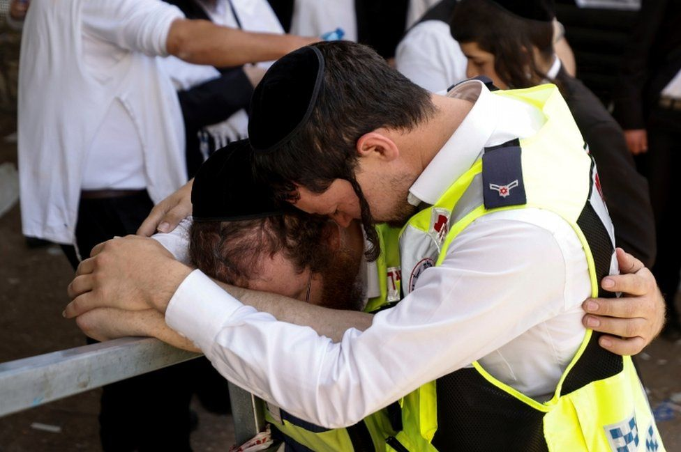 Emergency workers hug as they revisit at the site where dozens were crushed to death in a stampede at a religious festival, pictured on 2 May, 2021