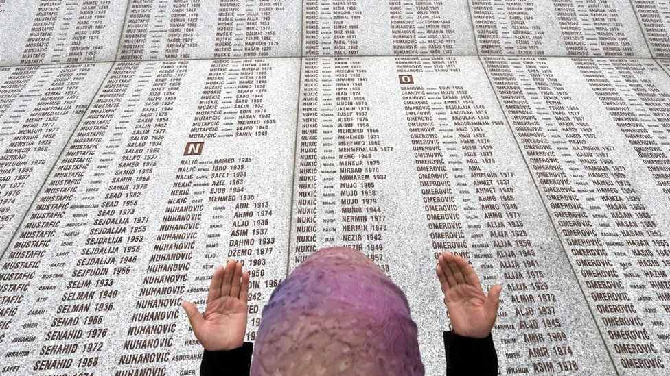 A Muslim woman prays near the list of victims of the Srebrenica massacre