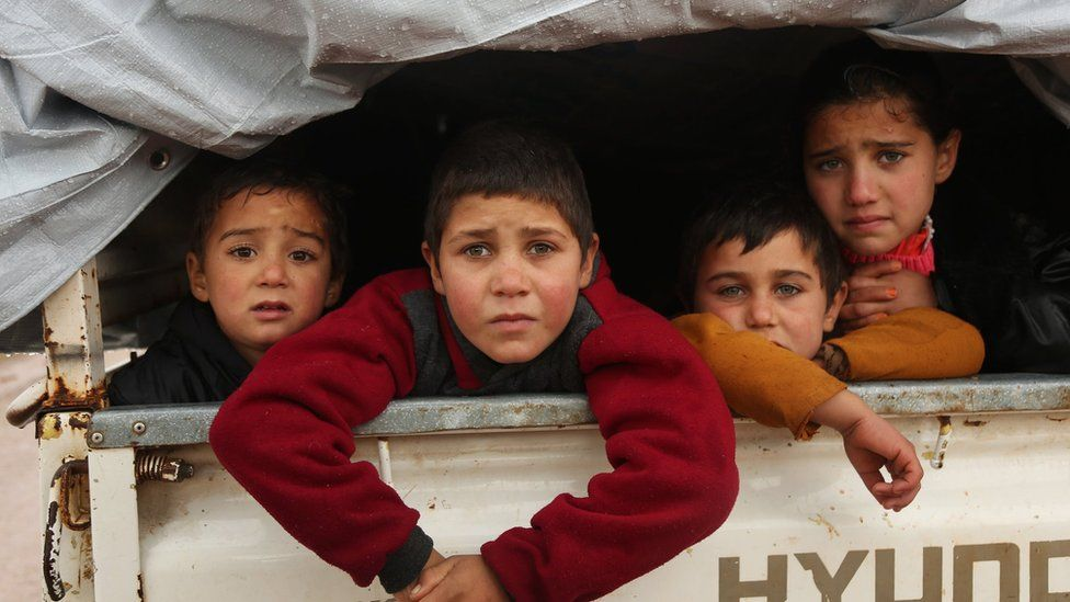 Syrian children sit in the back of a truck as they flee the fighting for Maarat al-Numan on 28 December 2019