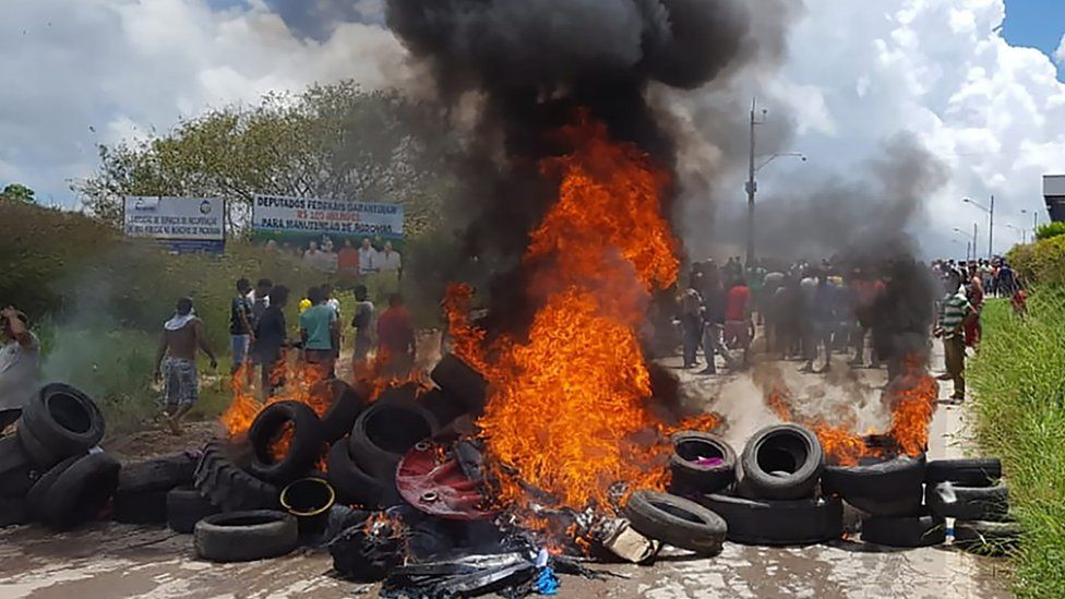 Residents of Pacaraima burn tyres and belongings of Venezuelans immigrants after attacking their makeshift camp on August 18, 2018
