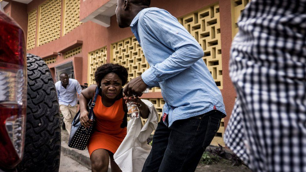 A woman runs for cover in Kinshasa