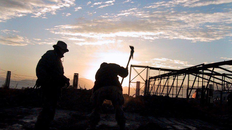 Soldados da 10ª Divisão de Montanha preparam terreno para enterrar um pedaço de entulho do World Trade Center no Campo Aéreo de Bagram, ao norte de Cabul, em 21 de dezembro de 2001