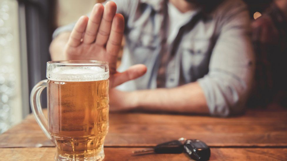 Man with drink and car keys