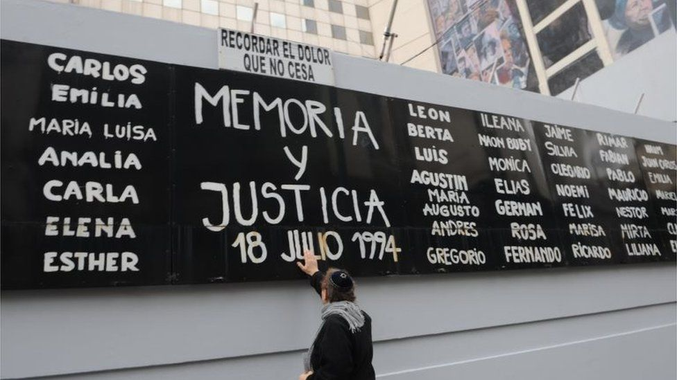 A man touches a billboard with the names of victims during an event to commemorate the 25 years of the attack against the Asociacion Mutual Israelita Argentina (AMIA), in Buenos Aires, Argentina, 18 July 2019