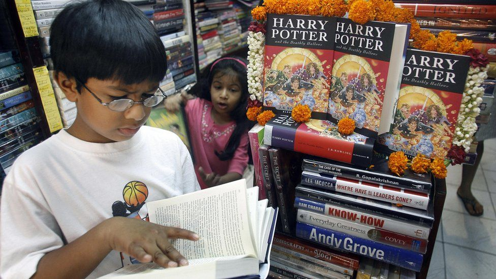 A young Indian boy reads a book next to a stack of Harry Potter books