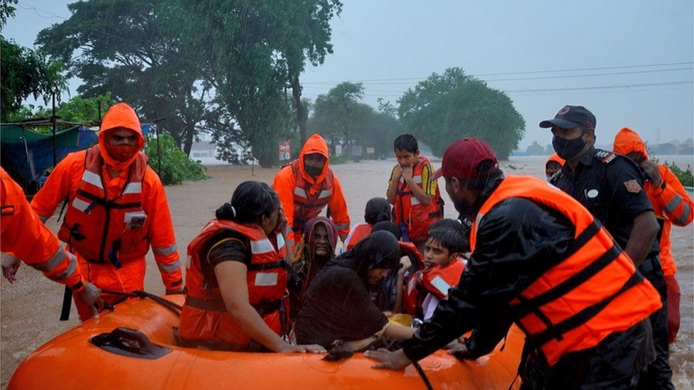 Rescuers carry resident from flooded areas in a dinghy, western India, July 2021
