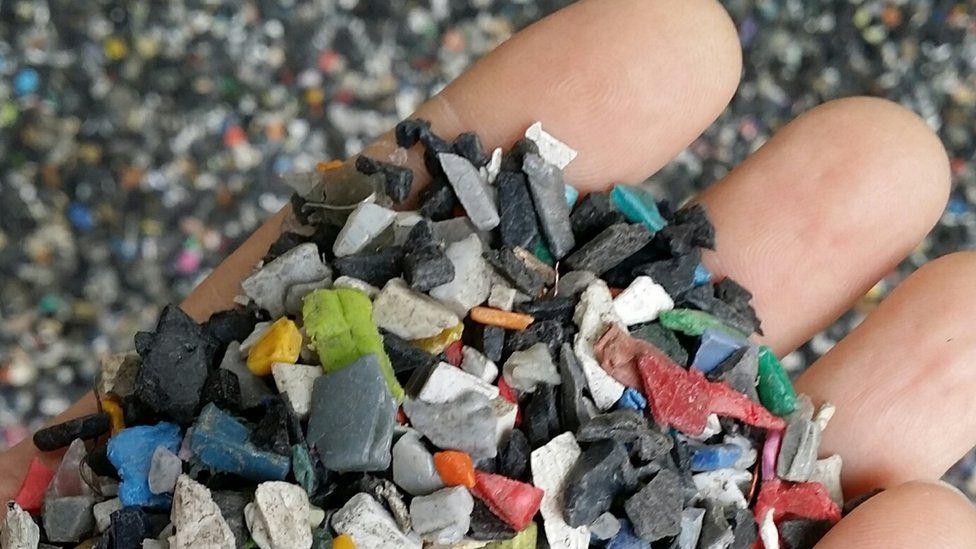 Hand holding shredded plastic