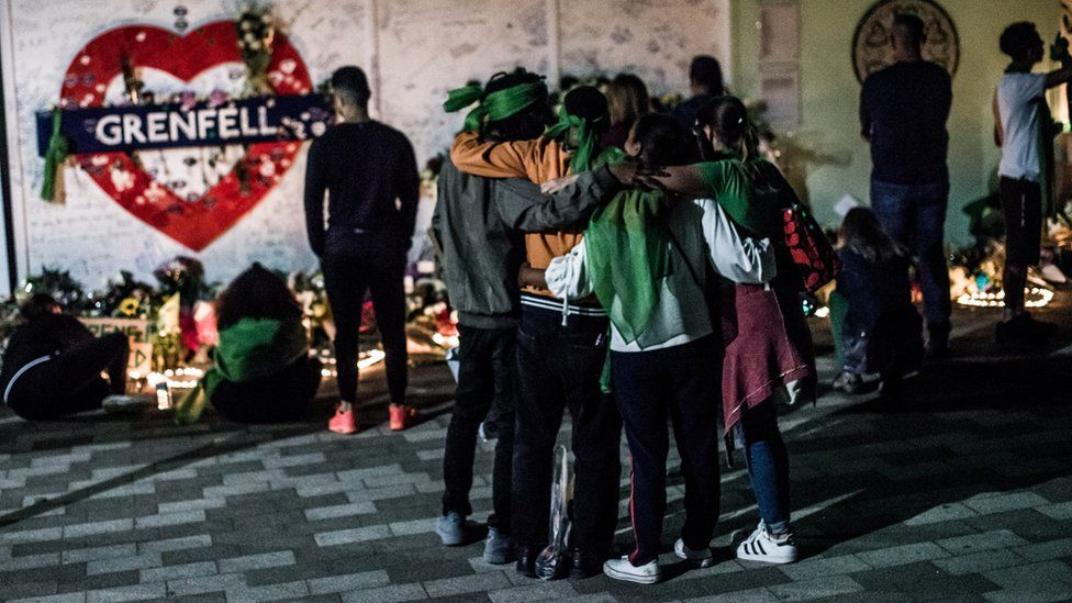 People embrace at the foot of the Grenfell Tower before a memorial