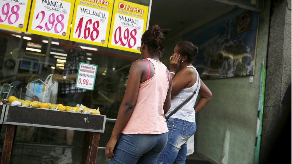 Women look at prices at a food market in Rio de Janeiro, Brazil