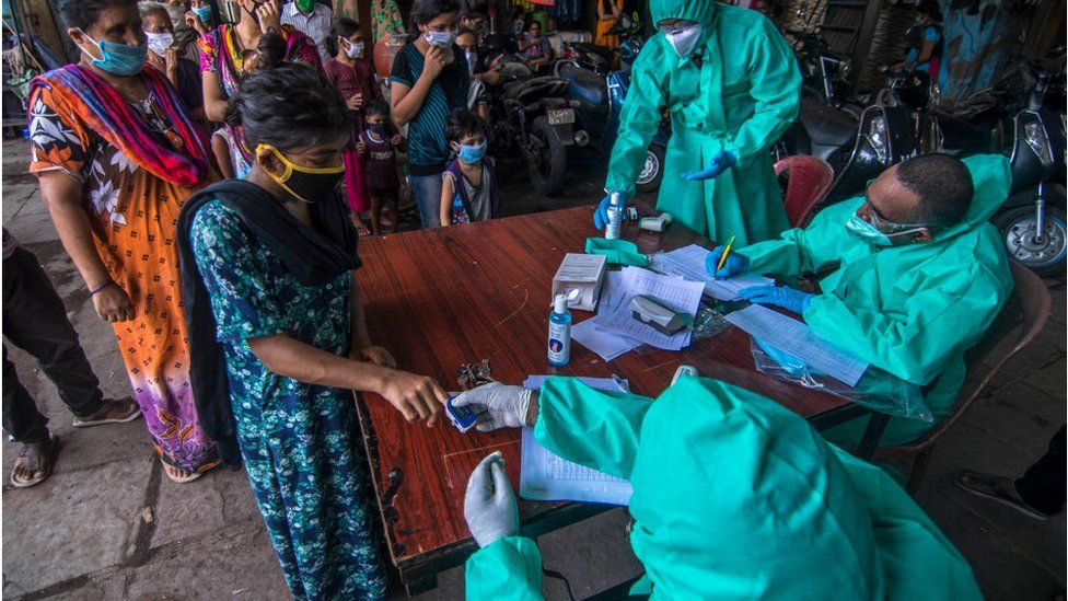 A team of doctors check the temperature and pulse rate of a local residents