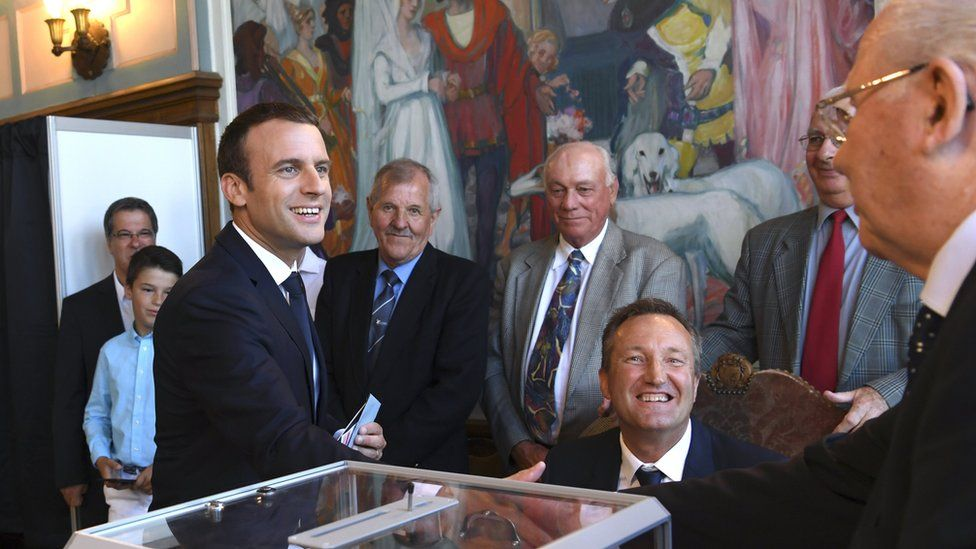 French President Emmanuel Macron (L) shakes hands with a voting official after voting in the second round of the French legislative elections at the City Hall in Le Touquet, France, 18 June 2017.