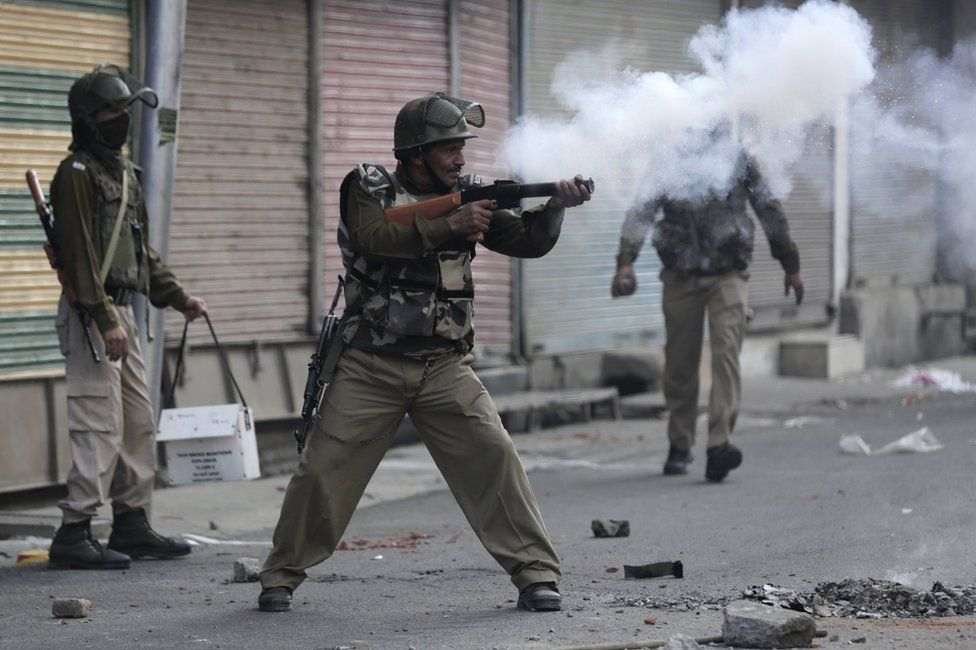 An Indian Paramilitary soldier fires tear gas at protesters