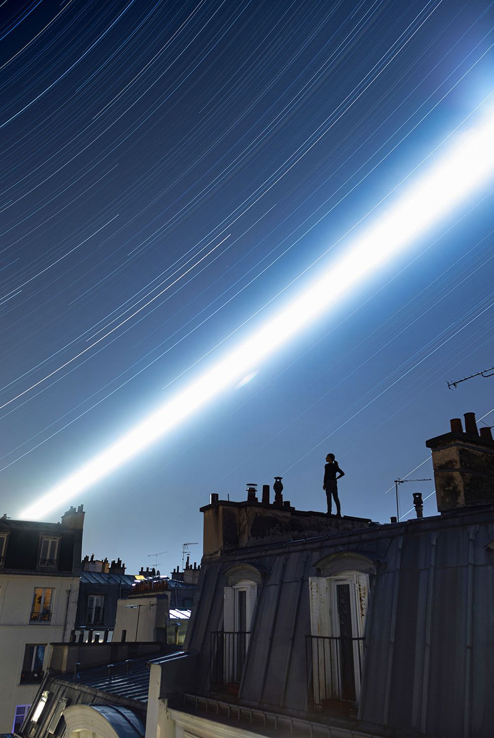 An image showing a woman standing on a Parisian rooftop with a long exposure view of the night sky