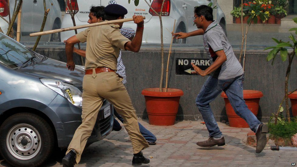 An Indian policeman uses a baton to disperse protesters during a clash between two groups in Ahmadabad, India, Tuesday, Aug. 25, 2015.