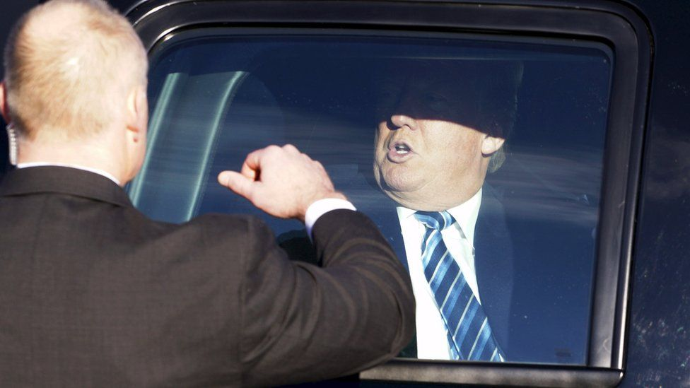 U.S. Republican presidential candidate Donald Trump prepares to leave his vehicle with a U.S. Secret Service agent preparing to open the door before Trump greets supporters at a polling place for the presidential primary in Manchester, New Hampshire February 9, 2016.